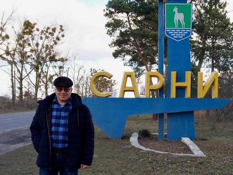 Тарас Владичук на фоні в'їздного знака в місто Сарни