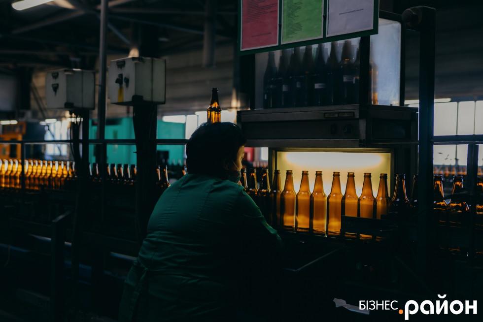 Працівниця стежить, аби не було пляшок з дефектами. Якщо такі є, одразу відкидає їх убік